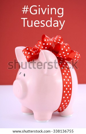 Gift wrapped piggy bank on red white background for Giving Tuesday savings concept.  - stock photo