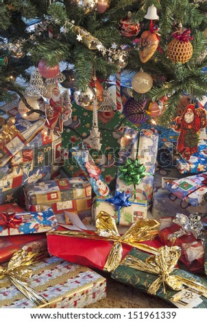 Gift wrapped presents below a Christmas tree  - stock photo