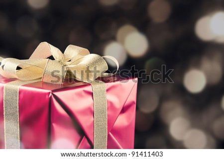 Gift wrapped with golden bow, bokeh background, copy space - stock photo