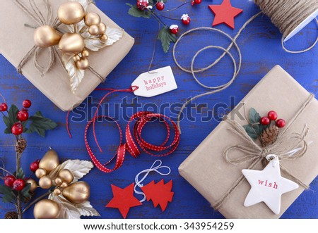 Gift wrapping presents in natural rustic theme brown kraft paper with string and ornaments on a dark blue rustic wooden table.  - stock photo