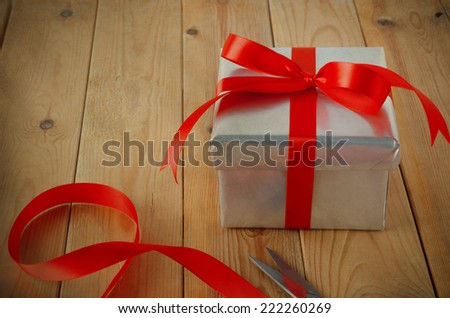 Gift wrapping scene. A Christmas gift box wrapped in silver paper and tied with red ribbon to a bow, on an old wood plank table with scissors and ribbon remnants.  Vintage style. - stock photo