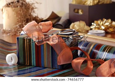 Gift wrapping still life with partially wrapped gift, ribbon and supplies.  Closeup with shallow dof. - stock photo