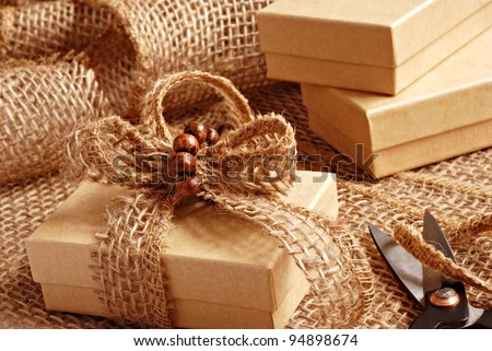 Gift wrapping still life with small brown boxes being decorated with eco friendly burlap ribbon and tiny wooden beads.  Macro with shallow dof. - stock photo