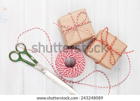 Gift wrapping with boxes and scissors over white wooden table - stock photo