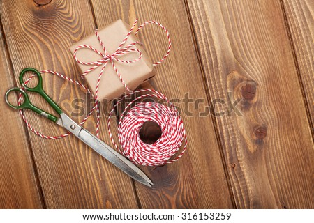 Gift wrapping with boxes and scissors over wooden table - stock photo