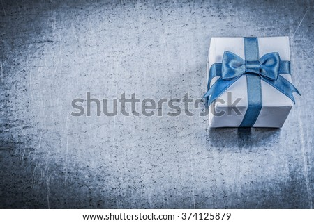 Giftbox present bow on metallic background holidays concept. - stock photo