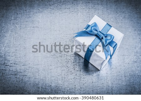 Giftbox with tied bow on metallic background holidays concept. - stock photo