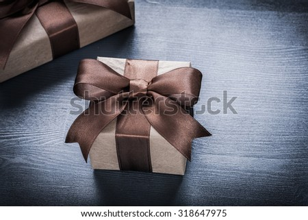 Giftboxes bows on vintage wooden board top view holiday concept.