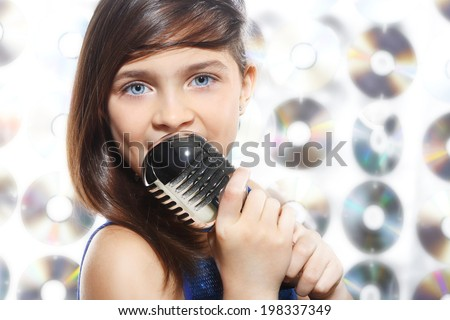 Gifted child. Child, teen, girl, singing into a microphone, a small singer  - stock photo