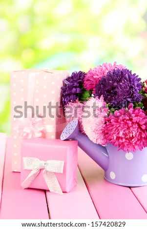 Gifts and flowers in watering can, on nature background