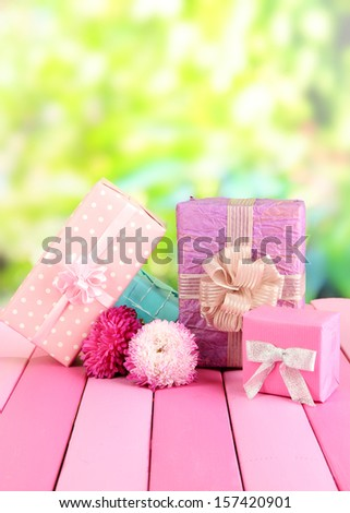 Gifts and flowers, on nature background - stock photo