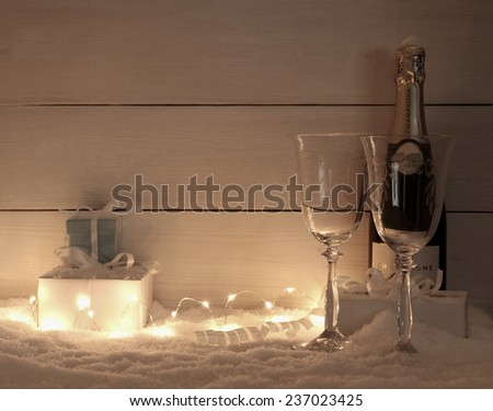 Gifts, Champagne glass and bottle on snow, in evening, fairy lights - stock photo
