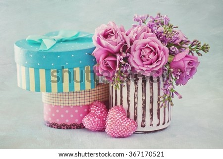 Gifts for a Valentine's Day or wedding on a blue background .Lilacs and pink roses flowers decorated with a heart.  - stock photo