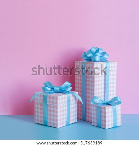 Gifts in a beautiful and elegant package on pink and blue background