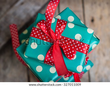 gifts in a beautiful and elegant package on the wooden table. red and turquoise colors. polka dots. top view - stock photo