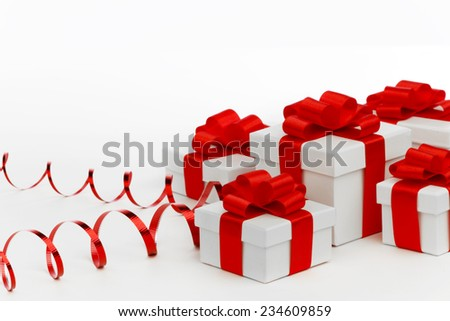 Gifts in white boxes with curly red ribbons isolated on white background - stock photo