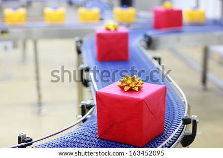 Gifts on conveyor belt in Christmas presents factory - stock photo