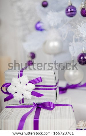 gifts white christmas tree with purple and silver toys  - stock photo