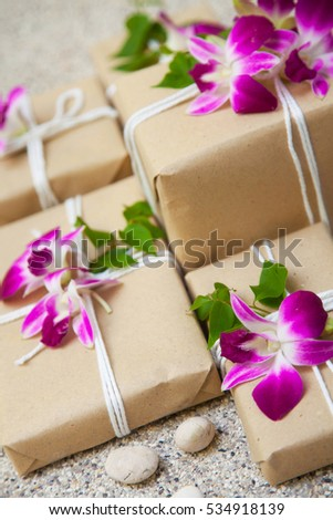 Gifts with orchids. Presents packaged in kraft paper.