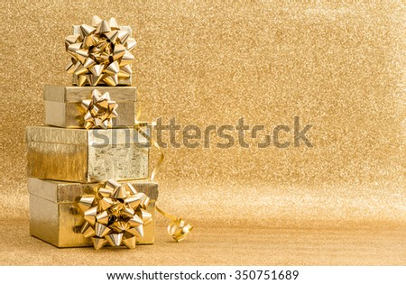 Gifts with ribbon bow on golden background. Holidays decoration - stock photo