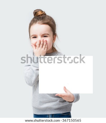 Giggles happy kid girl closes face with her hand. Confused little girl holding a poster for your information. Gray background do not speak