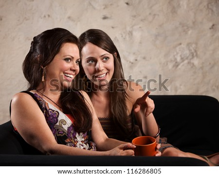 Giggling European women looking ahead and pointing - stock photo