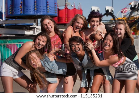 Giggling group of teenage girls at a theme park - stock photo