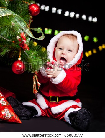 Giggling Santa baby sitting beside Christmas tree