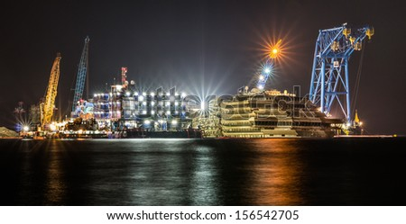 GIGLIO ISLAND, ITALY - SEPTEMBER 28: spectacular night view of the wreck of Costa Concordia on September 28, 2013 in Giglio Island, Italy. This is how it looks after the recent successful parbuckling.