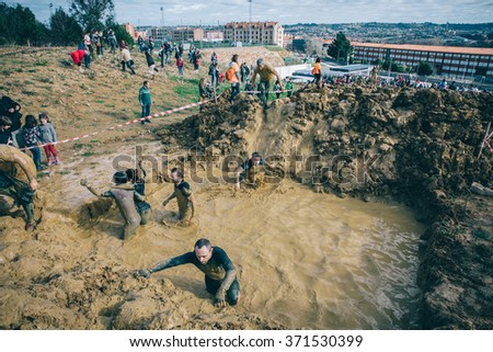 GIJON, SPAIN - JANUARY 31, 2016: Runners into the Farinato Race event, a extreme obstacle race, celebrated in Gijon, Spain, on January 31, 2016. Participants crossing a mud pit in a test of the race. - stock photo