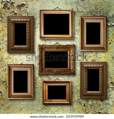 Gilded wooden frames for pictures on old  rusty metallic wall