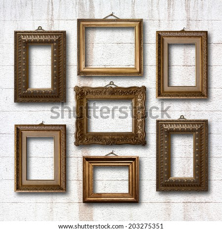 Gilded wooden frames for pictures on old stone wall - stock photo