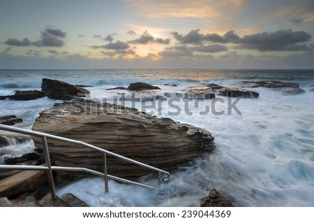 Giles Baths  at Coogee  is known as a bogey hole - a semiformal rock pool open to the surging surf.  Serene and idyllic at low tide but transforms into a raging whitewater in high turbulent seas. - stock photo
