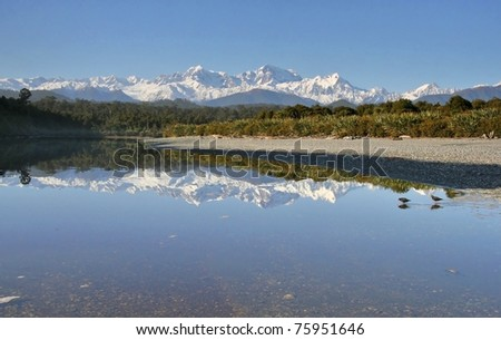 Gillespies Lagoon on the West Coast of New Zealand, reflecting Mt. Cook and Mt. Tasman, New Zealand's highest mountains.