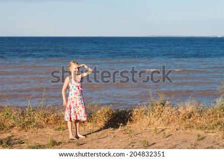 gilrl looking forward on the seashore - stock photo