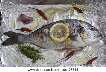 Gilt-head sea bream (sparus aurata) with lemon, herbs, garlic and chili on aluminum foil ready to be cooked - stock photo