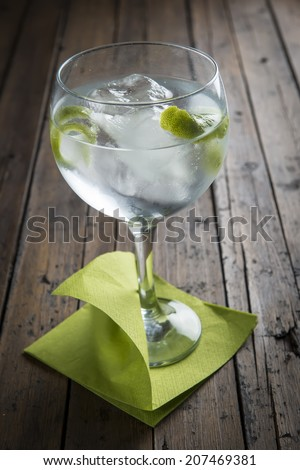 Gin and tonic garnished with lime on a wooden background - stock photo