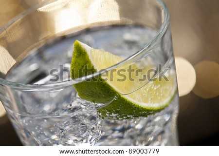 Gin Tonic Cocktail in front of a brown gold background - stock photo