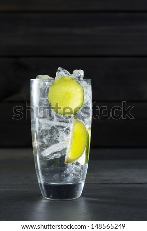 Gin tonic cocktail with lima and ice cube on black slate stone background - stock photo