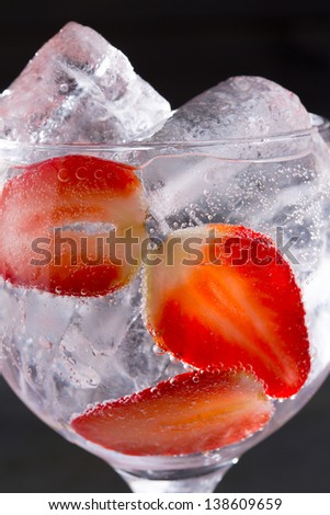 Gin tonic cocktail with strawberries ice macro closeup on black - stock photo