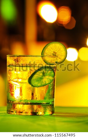 Gin tonic coctail with colorful bokeh. Long exposure shot. - stock photo