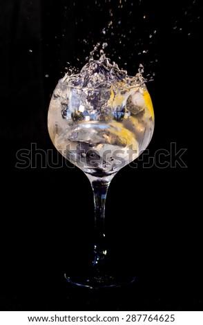 Gin tonic splash against black background - stock photo