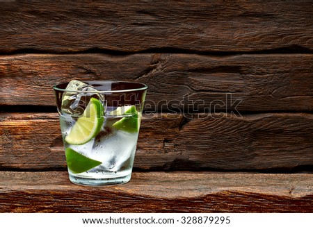 Gin tonic with lime wedges on wooden table and background - stock photo
