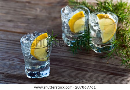 Gin with lemon and ice on a old wooden table - stock photo
