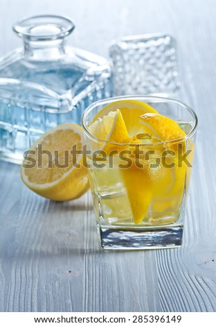 gin with lemon and ice on  old wooden table - stock photo