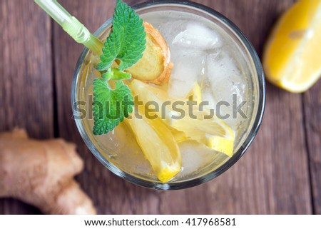Ginger ale soda with lemon, mint, ginger and ice over rustic wooden background - stock photo