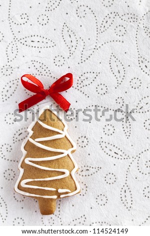Ginger and Honey cookie in the shape of a Christmas fir tree with white sugar decoration and red bow on the white texturized paper background. - stock photo