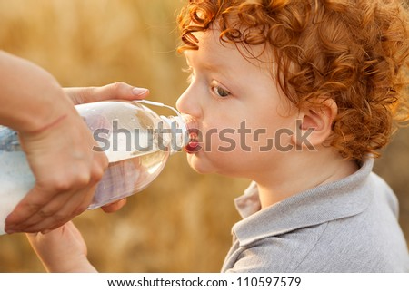 Ginger baby boy drinking water from bottle in the wheat field [Approx. 3 years] - stock photo