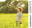 ginger baby boy standing in the field of yellow flowers and sreaming (shouting). outdoor shot - stock photo