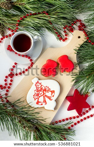 Ginger biscuits and a Cup of tea on the table with branches of spruce. Selective focus. Christmas concept.